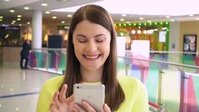 走与在购物中心的智能手机的美丽的妇女在慢动作 浏览互联网和聊天 股票录像