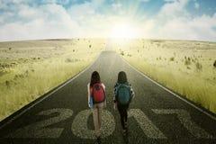 走与在路的日出的两名学生 免版税库存照片
