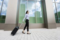 走与在边路的行李的年轻亚裔女实业家全长侧视图反对大厦 免版税库存照片