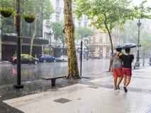 走与在重的暴雨的伞的人们在市中心 免版税库存照片