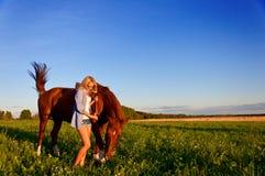 走与在领域的一匹马的女孩 免版税库存照片