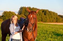 走与在领域的一匹马的女孩 图库摄影