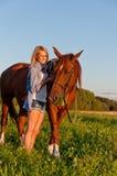 走与在领域的一匹马的女孩 免版税库存图片