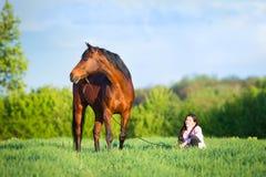 走与在领域的一匹马的年轻美丽的女孩 库存照片