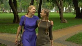 走与女儿的愉快的母亲在公园、友谊、信任和家庭团结 影视素材