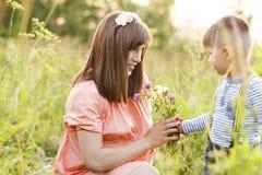走与她的儿子的美丽的孕妇 免版税库存图片