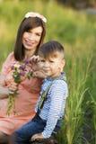 走与她的儿子的美丽的孕妇 免版税图库摄影