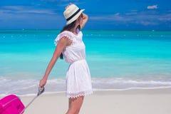 走与她的在热带海滩的行李的年轻美丽的妇女 库存图片