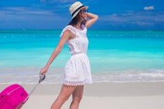 走与她的在热带海滩的行李的年轻美丽的妇女 图库摄影