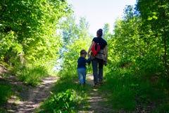 走与她的小儿子的年轻母亲户外在夏天 免版税库存图片