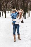 走与她的婴孩的愉快的年轻母亲在公园在冬天 免版税库存照片