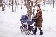 走与婴儿推车的妇女在森林里在冬天 免版税库存图片