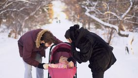 走与婴儿推车的婴孩的年轻夫妇在冬天 年轻已婚夫妇调查婴儿推车对愉快的婴孩一会儿 影视素材