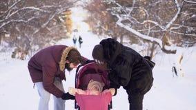 走与婴儿推车的婴孩的年轻夫妇在冬天 年轻已婚夫妇调查婴儿推车对愉快的婴孩一会儿 股票录像