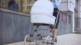 走与婴儿车的夫人谈的电话在商业中心,多任务附近 股票视频