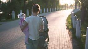 走与婴孩的母亲在手和婴儿车,太阳上是光亮的 股票录像
