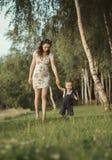 走与孩子的怀孕的妈妈 免版税库存图片