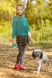 走与宠物的白肤金发的女孩在秋天庭院里 库存图片