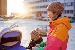 走与小儿童婴儿推车的年轻母亲在冬天在日落 免版税图库摄影