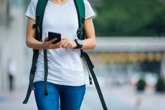 走与巧妙的电话的妇女在现代城市 免版税库存照片