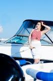 走与帽子和袋子的年轻美丽的妇女在船坞 免版税库存照片