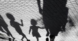 走与成人的一个小男孩和女孩的模糊的阴影 免版税库存照片