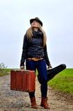 走与手提箱和小提琴的妇女 免版税库存图片