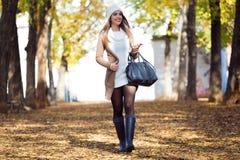 走与手机的美丽的女孩在秋天 库存照片