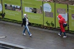 走与敞篷的妇女在下雨天湿街道期间,在fischerinsel的工程项目 免版税库存照片