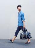 走与旅行袋子的一个年轻人的侧视图画象 图库摄影