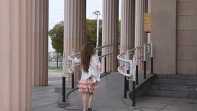走与柱子的舷梯的女孩在背景中 影视素材