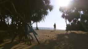 走与沿热带海滩的背包的年轻人到达海洋和上升胳膊 努力去做在含沙岸的男性远足者 影视素材
