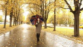 走与沿秋天胡同的伞的美丽的孕妇在一个雨天 免版税库存图片
