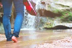 走与牛仔裤的妇女和运动鞋鞋子和瀑布背景、概念旅行、软性和精选的焦点 免版税库存图片