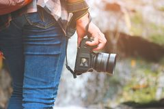 走与牛仔裤的妇女和运动鞋鞋子和瀑布背景、概念旅行、软性和精选的焦点 免版税图库摄影