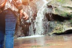 走与牛仔裤的妇女和运动鞋鞋子和瀑布背景、概念旅行、软性和精选的焦点 库存照片
