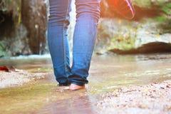 走与牛仔裤的妇女和运动鞋鞋子和瀑布背景、概念旅行、软性和精选的焦点 图库摄影