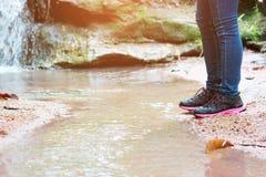 走与牛仔裤的妇女和运动鞋鞋子和瀑布背景、概念旅行、软性和精选的焦点 库存图片