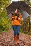 走与狗和伞 免版税库存照片