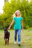 走与狗或短毛猎犬的白肤金发的女孩 免版税库存图片
