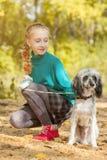 走与狗的可爱的女孩在秋天公园 免版税图库摄影