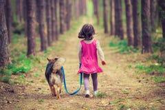 走与狗的小女孩 免版税库存图片