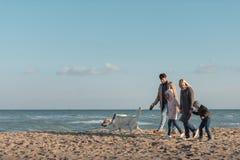 走与狗的幸福家庭在海边 图库摄影