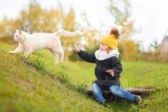 走与猫的逗人喜爱的小孩女孩户外,冷的天 库存照片