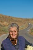 走与甜微笑的老传统希腊妇女在希腊 免版税库存图片