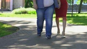 走与红色礼服的,身体正面亭亭玉立的可爱的妇女的超重人 股票视频