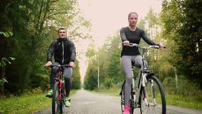 走与自行车和饮用水的有吸引力的夫妇在森林里 股票视频