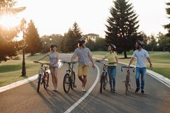 走与自行车的小组快乐的骑自行车者击倒路 库存照片