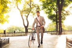 走与自行车的确信的商人 免版税库存图片