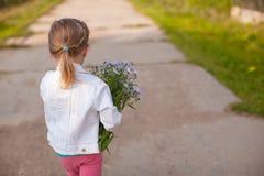走与花花束的小逗人喜爱的女孩  免版税库存图片